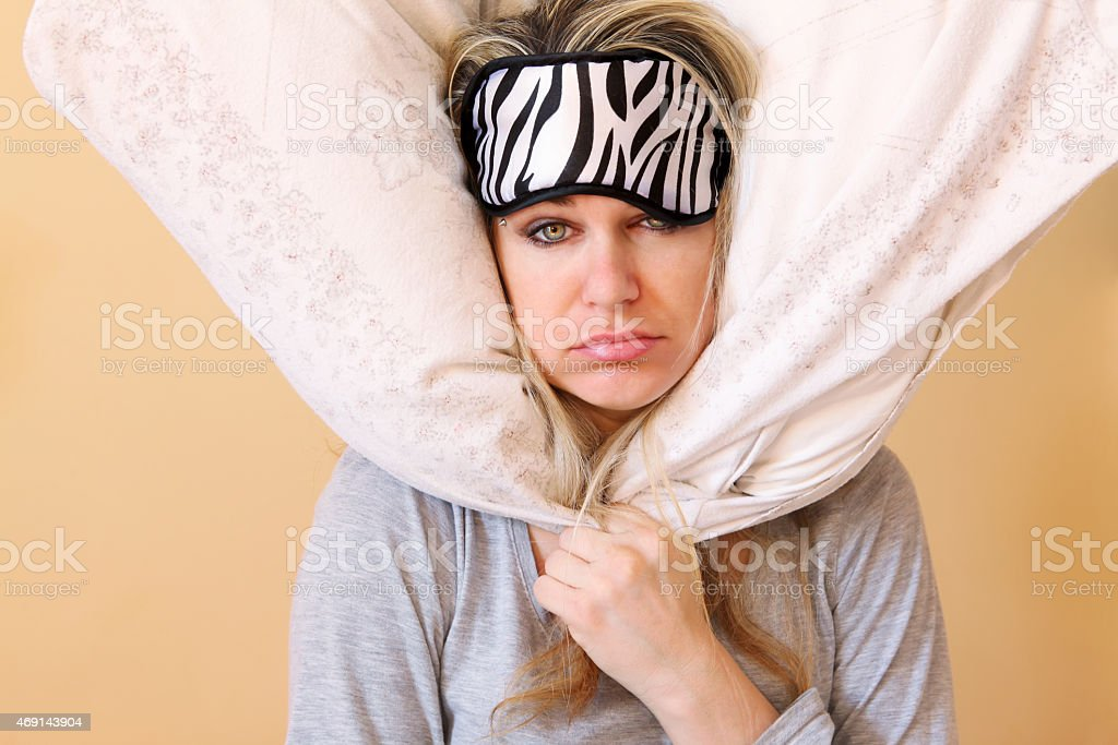 Sick woman with a sleep mask and a pillow around her head stock photo