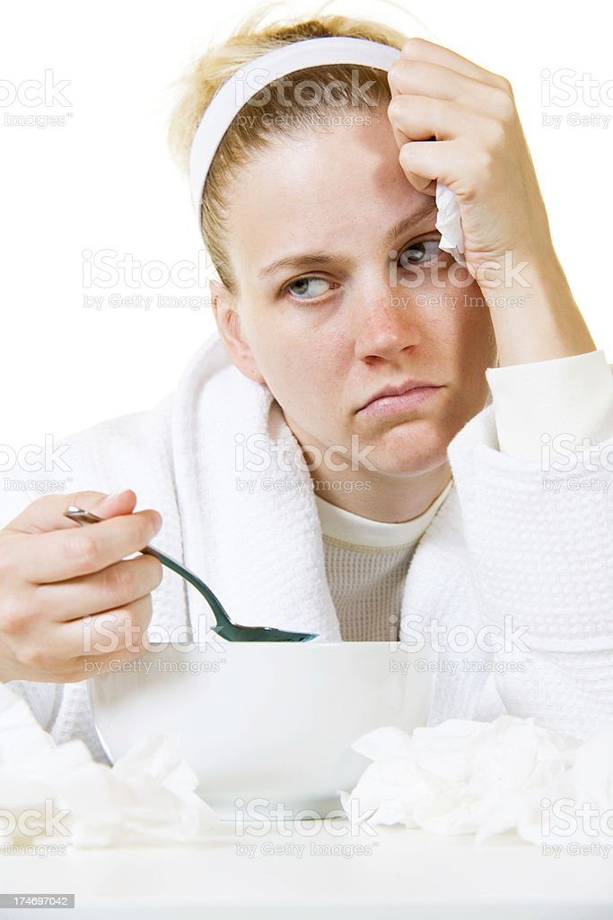 Sick Woman with Cold and Tissues Eating Soup stock photo