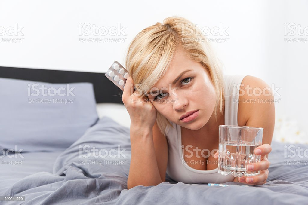 sick woman with pack of pills lying on bed stock photo