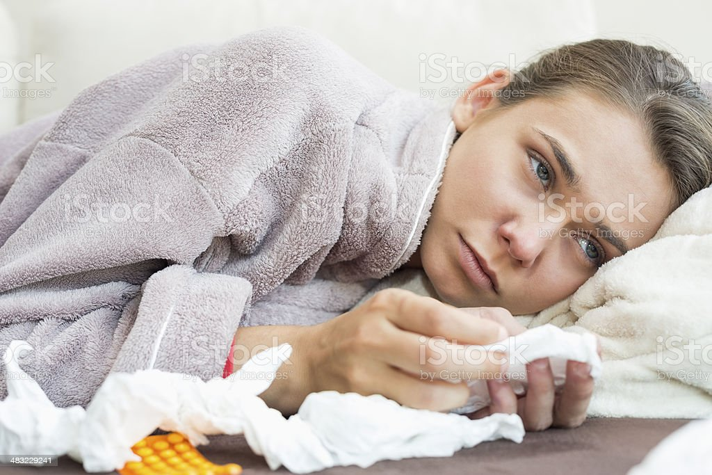 Sick woman with tissue and medicines lying on bed stock photo