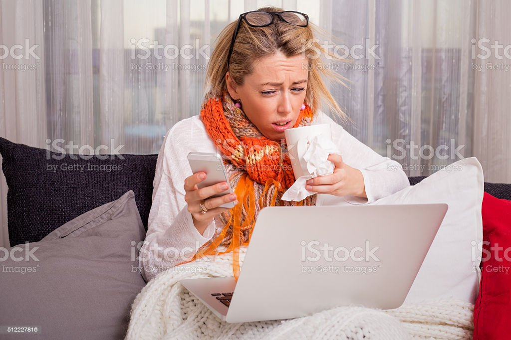 Sick woman working on laptop stock photo