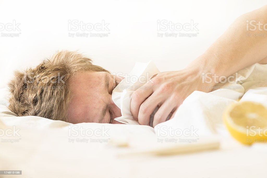 Sick young man resting in bed with tissue stock photo