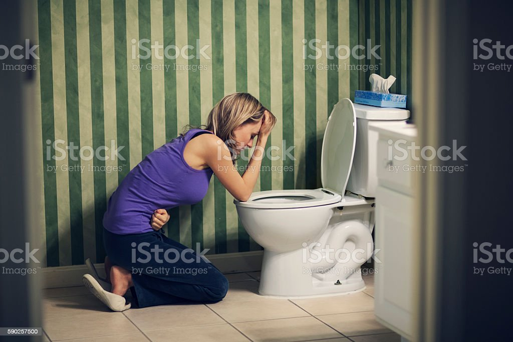 Sick young woman at toilet stock photo
