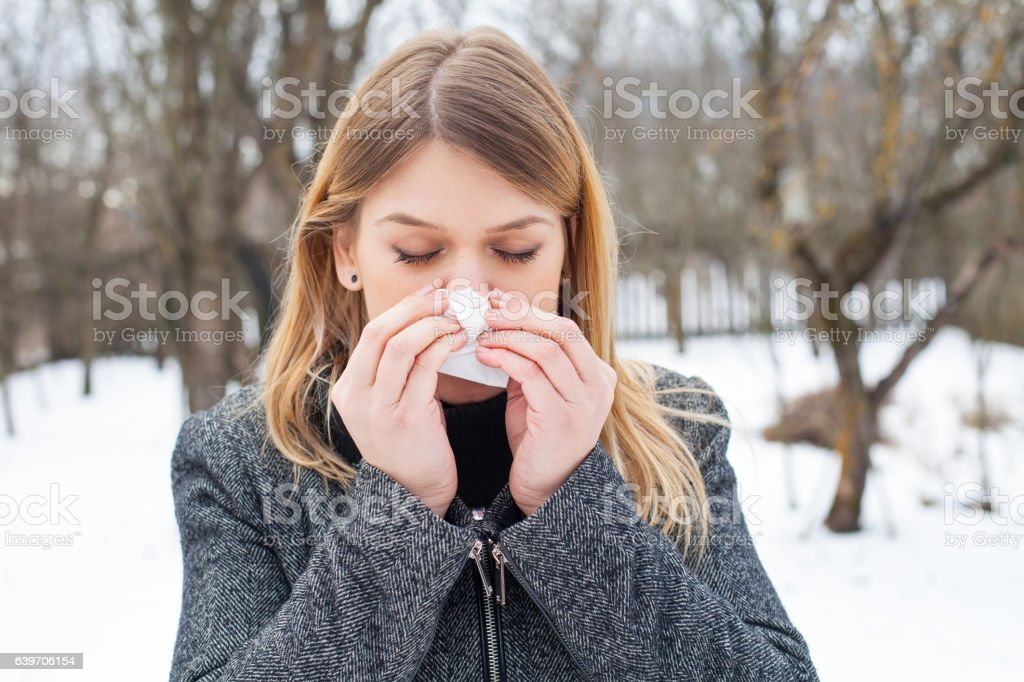 Sick young woman blowing her nose stock photo