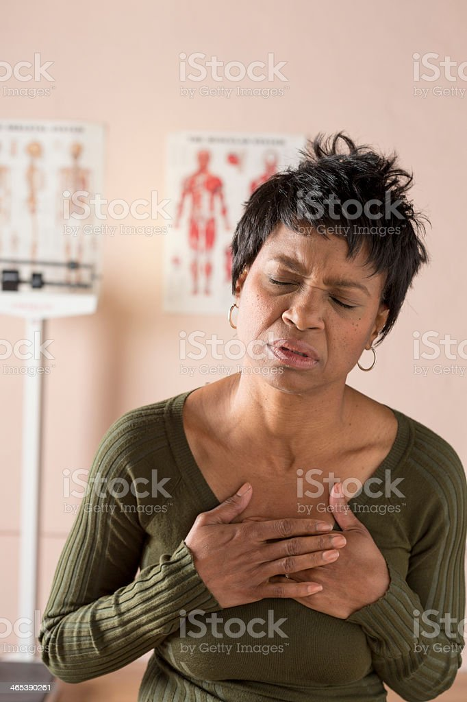Sickly woman at the doctor's office holding her chest stock photo