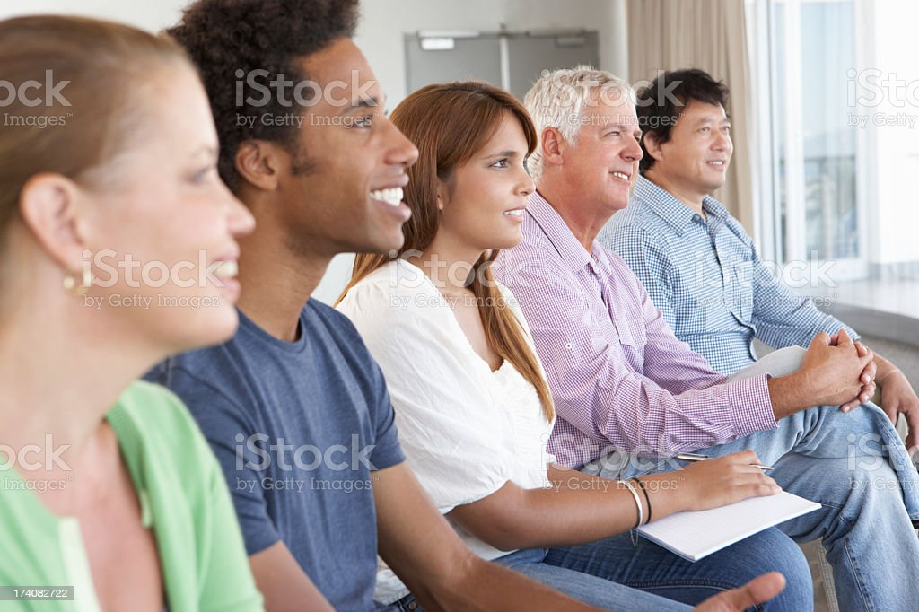 Side angle view of a support group full of smiling people stock photo