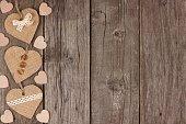 Side border of handmade burlap heart decorations over rustic wood