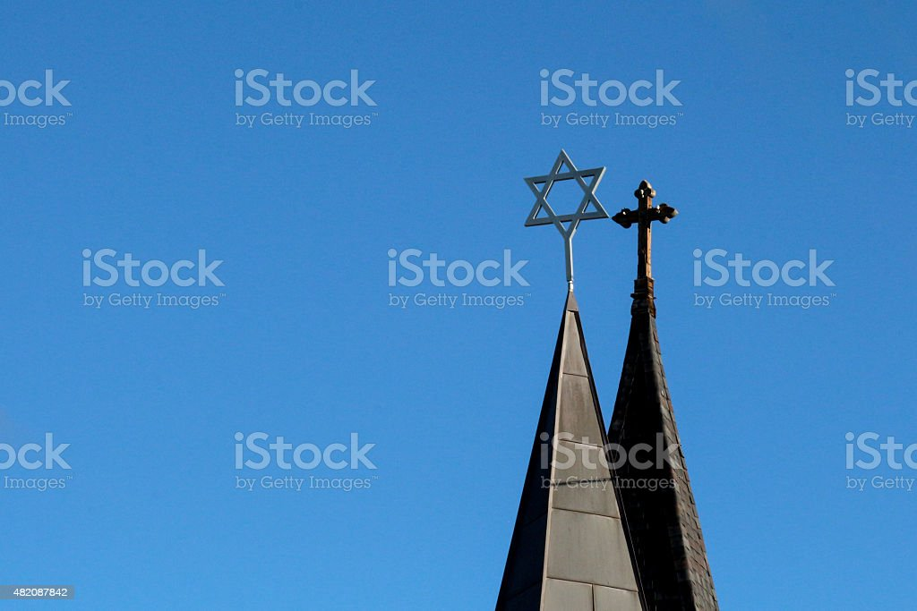 Side by side spires with cross and star of david stock photo