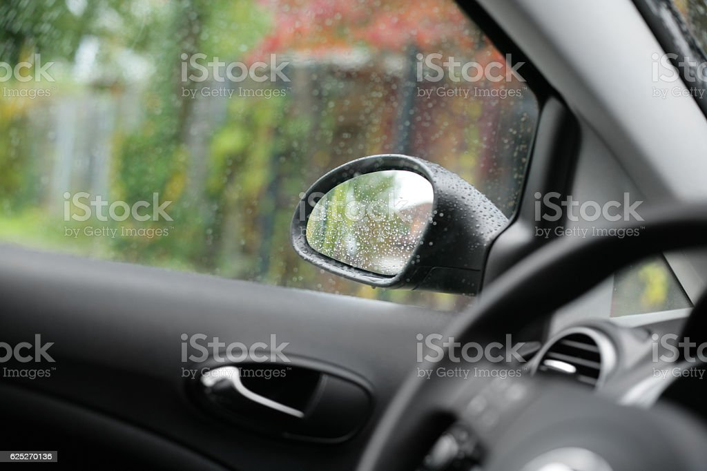 Side car mirror glass with rainy drops stock photo