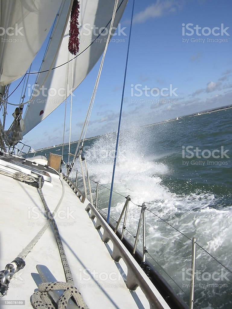 Side deck of a sailboat crashing waves royalty-free stock photo
