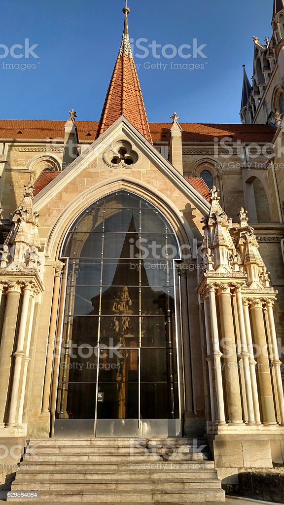 Side entrance Cathedral of Lausanne and reflection of statues architecture stock photo