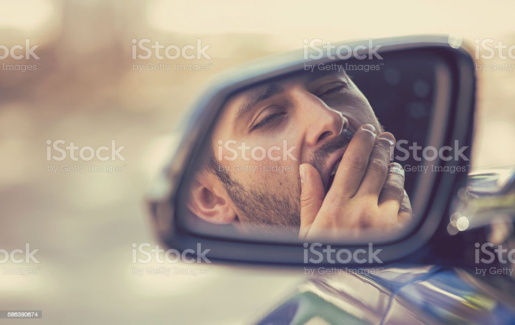 Side mirror view sleepy tired yawning man driving car stock photo