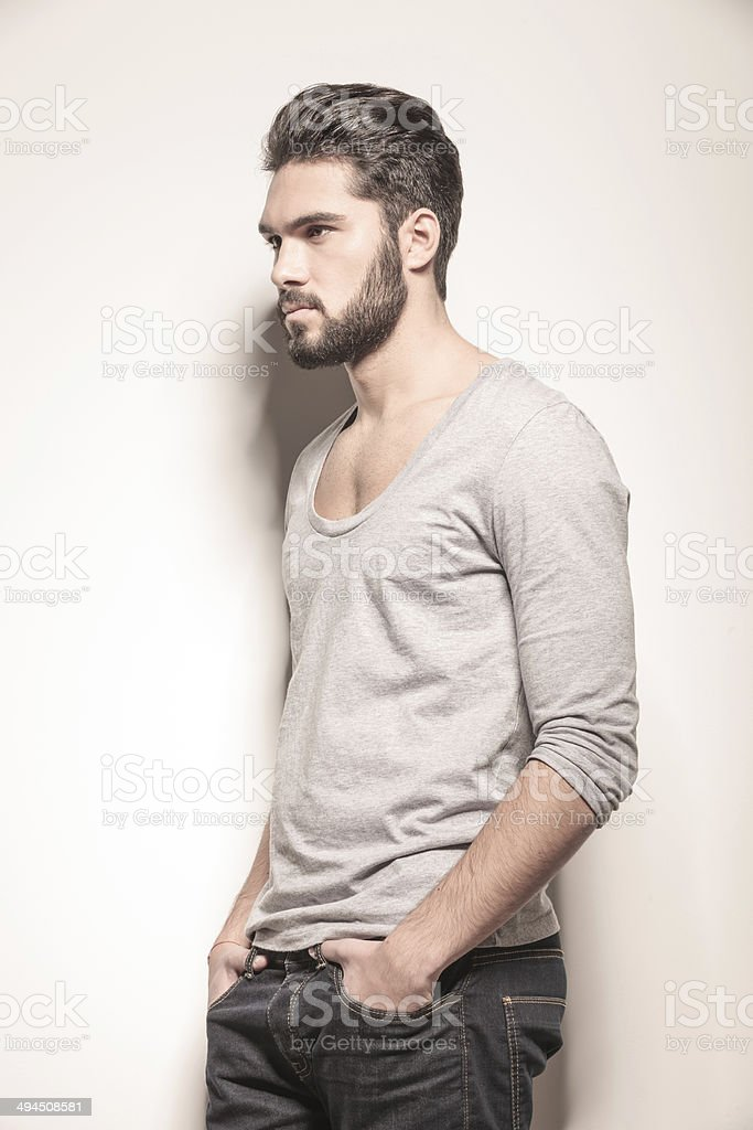 side of a  man with hands in his pockets stock photo