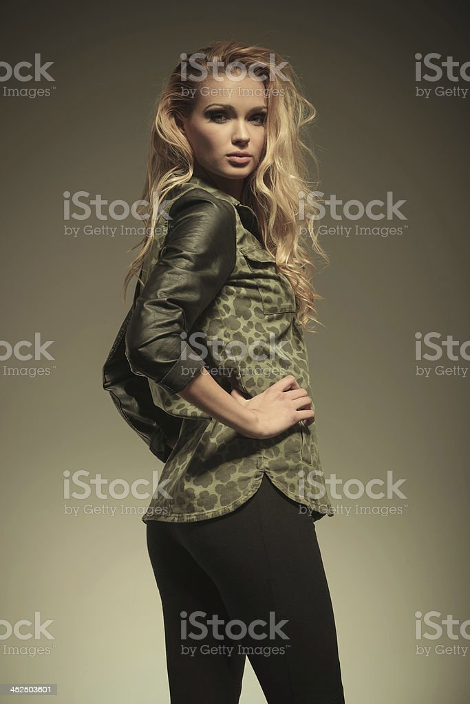 side of a sexy blonde woman in leather pants posing stock photo