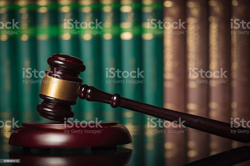 side of  judge's gavel in front of law books stock photo