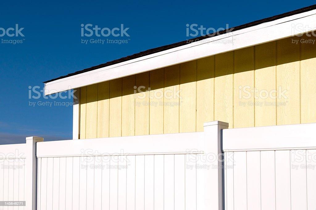 Côté de Yellow maison avec clôture blanche photo libre de droits