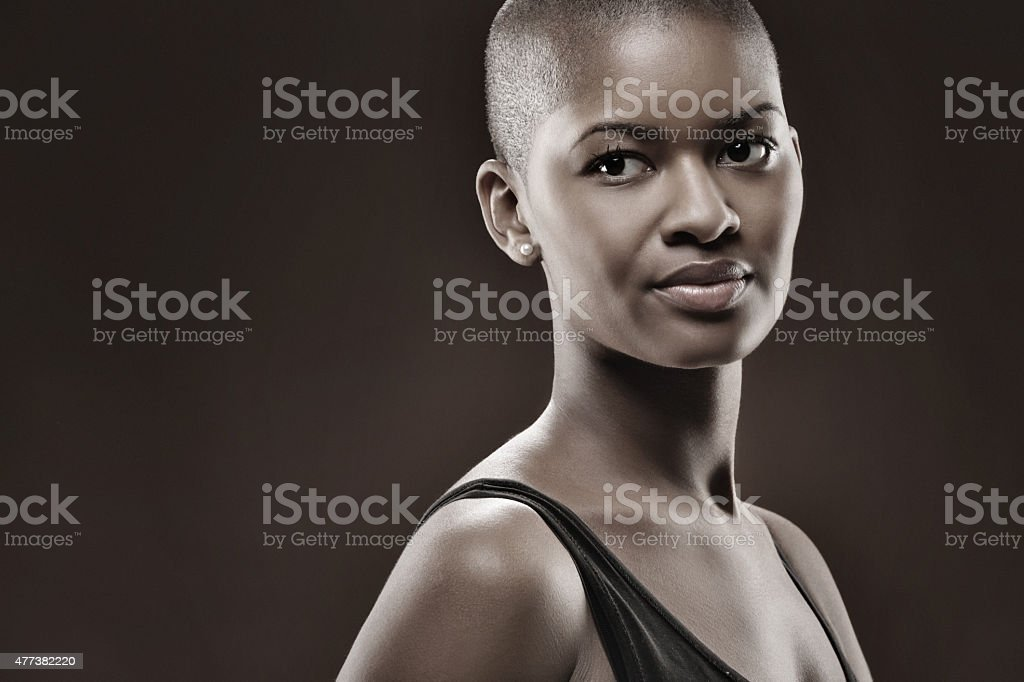 Side on view of a shaven headed black female stock photo