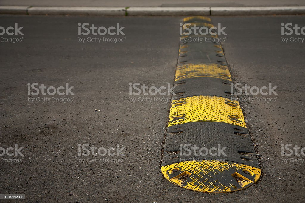 Side on view of rubber black and yellow speed bump stock photo