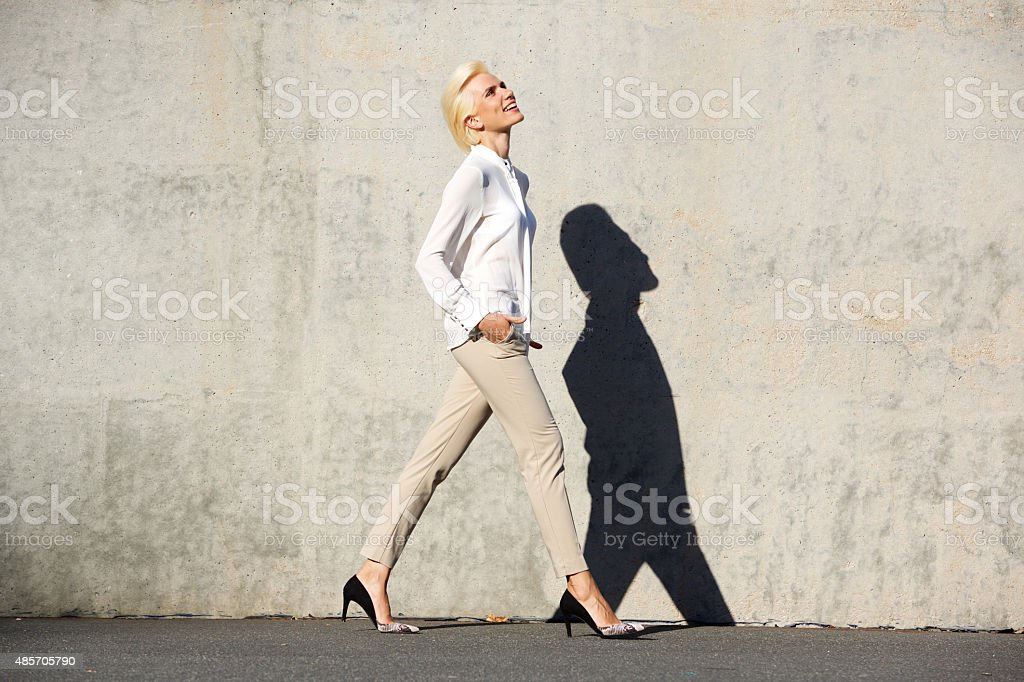 Side portrait of a cheerful young woman walking outside stock photo