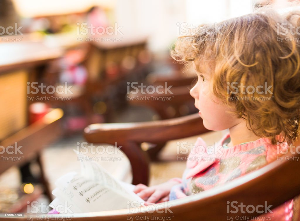 Side profile of a seated child reading a musical book royalty-free stock photo