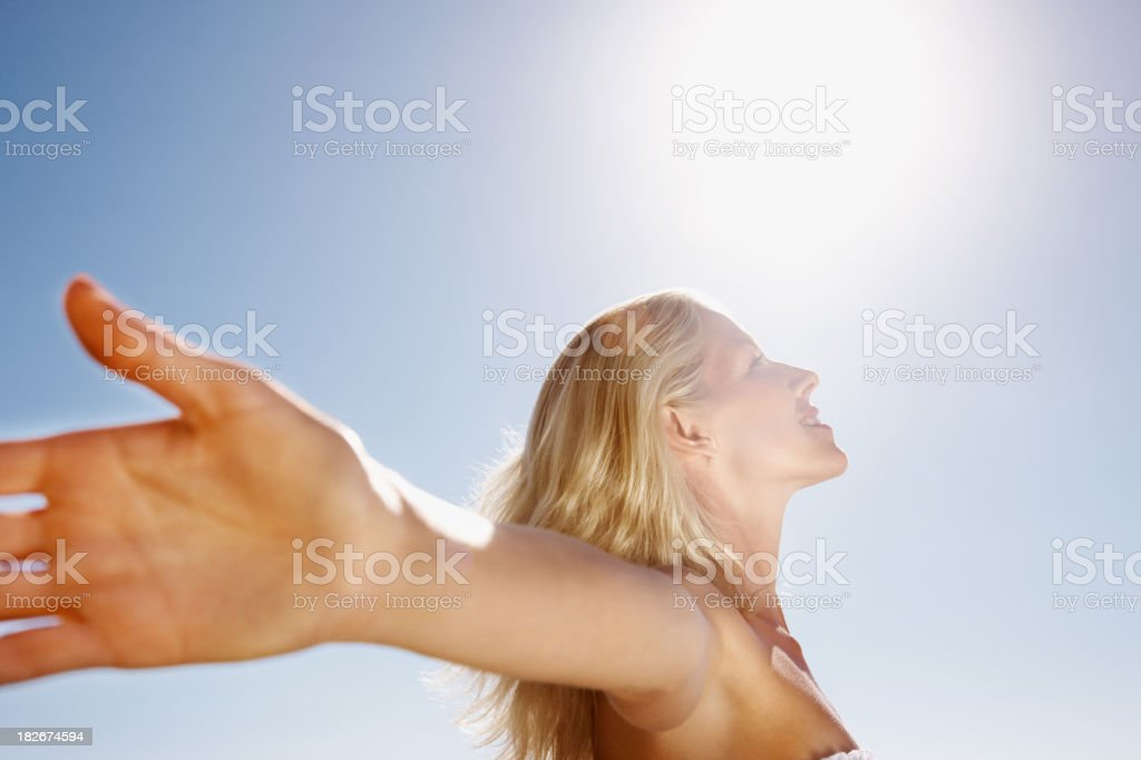 Side profile of a woman with arms outstretched stock photo