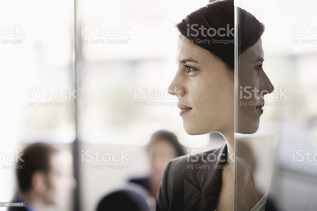 Side profile on a businesswoman with coworkers in the background stock photo