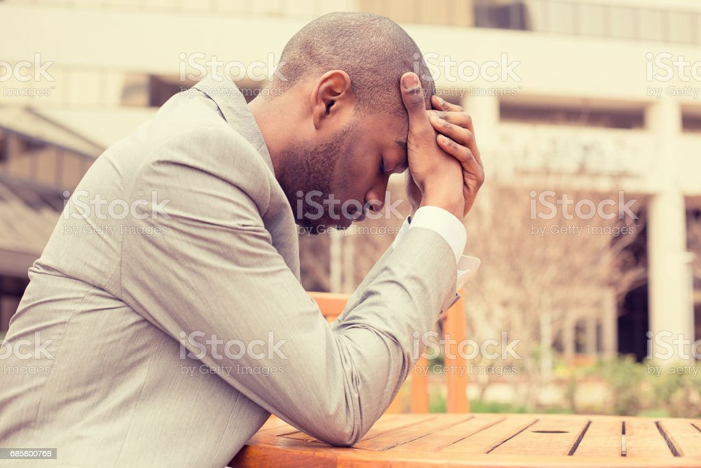 side profile stressed young businessman sitting outside corporate office holding head with hands looking down stock photo