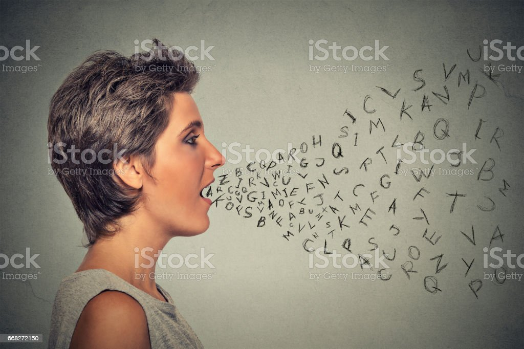 Side profile woman talking with alphabet letters coming out of her mouth stock photo