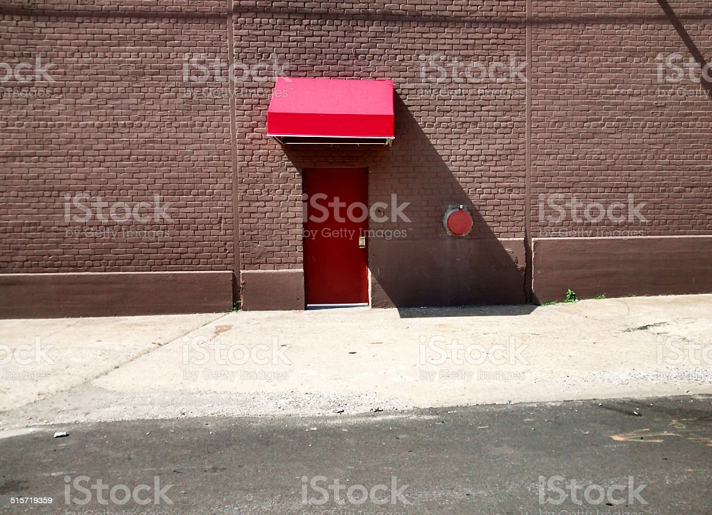 Side red brick building red door and red awning daytime stock photo