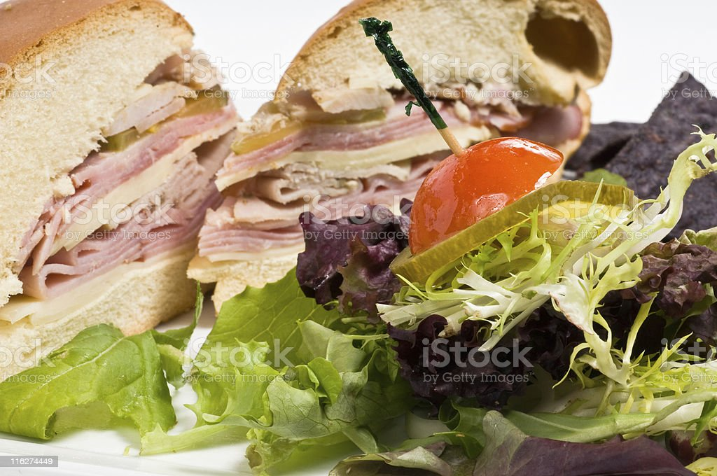 A side salad next to a meat-filled sandwich cut in half. stock photo