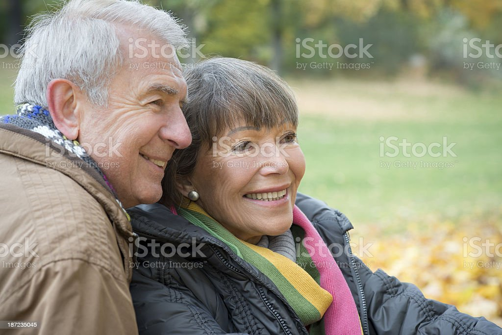 Side view at smiling Senior couple sitting outdoors in autumn royalty-free stock photo