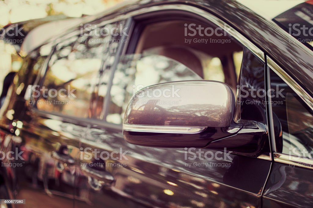 Side view mirror and side view of luxury car. selective focus. stock photo