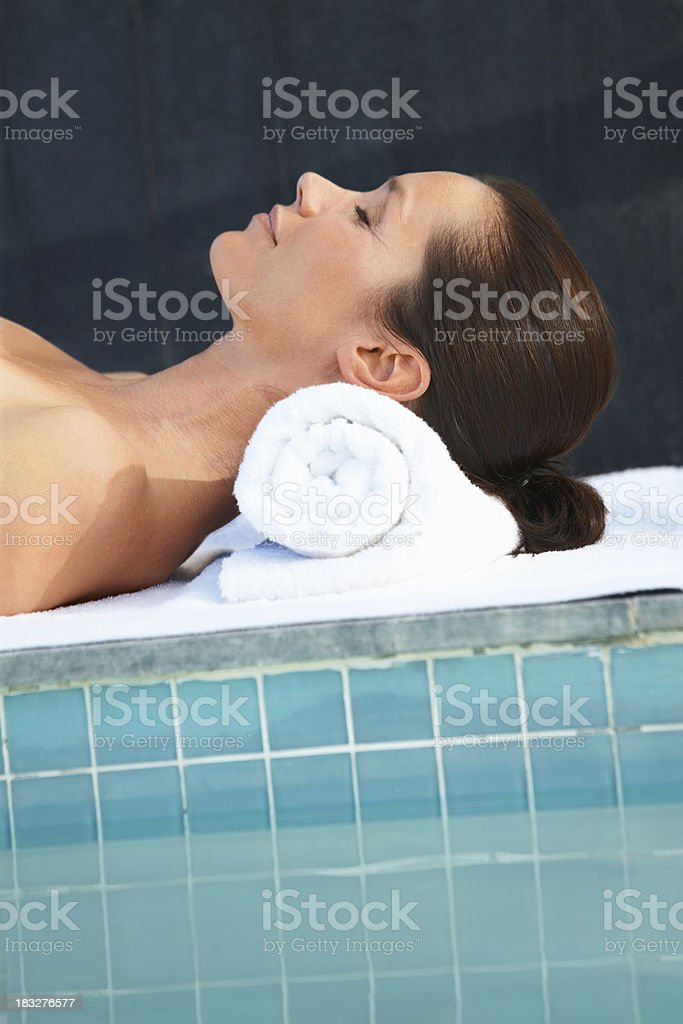 Side view of a beautiful woman resting by swimming pool royalty-free stock photo