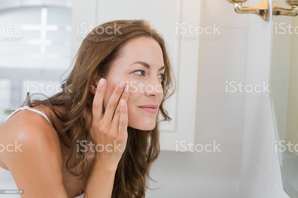 Side view of a beautiful young woman examining her face stock photo