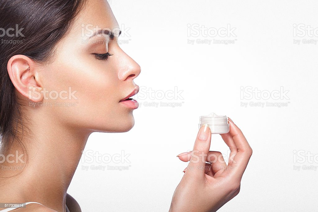 Side view of a beautiful young woman holding moisturizing cream stock photo