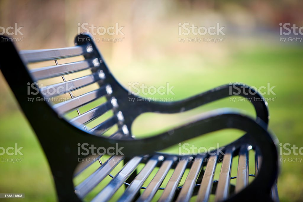 Side view of a black park bench with grass in background stock photo