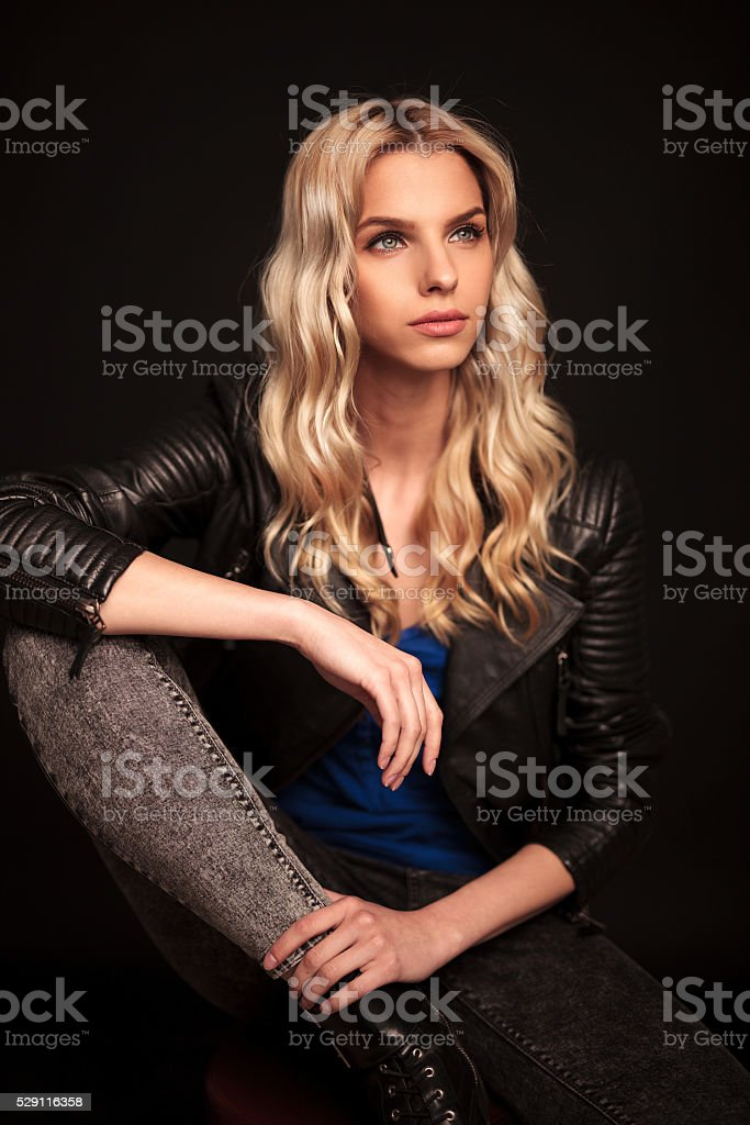 side view of a blond woman in leather jacket sitting stock photo