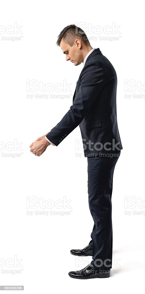 Side view of a businessman looking downwards and holding something stock photo