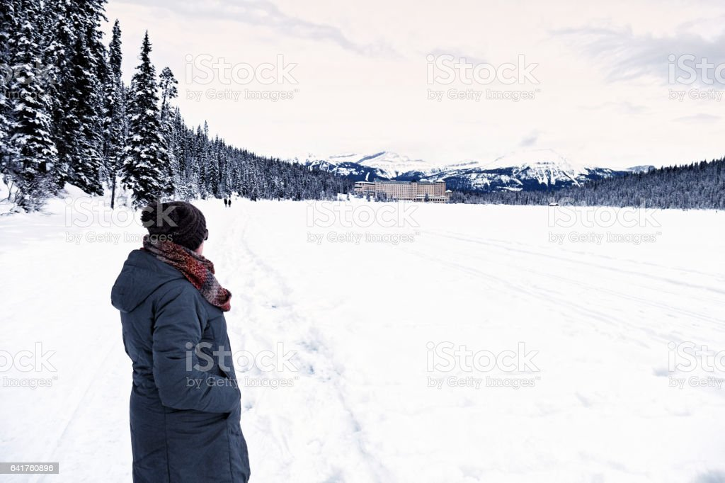Side view of a caucasian woman with winter clothing , looking at the Fairmont Chateau Lake Louise,Banff National Park,Alberta,Canada stock photo