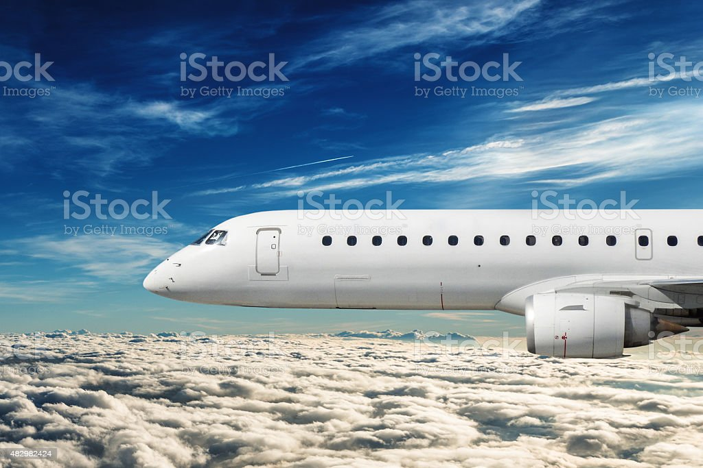 side view of a commercial airplane flying stock photo