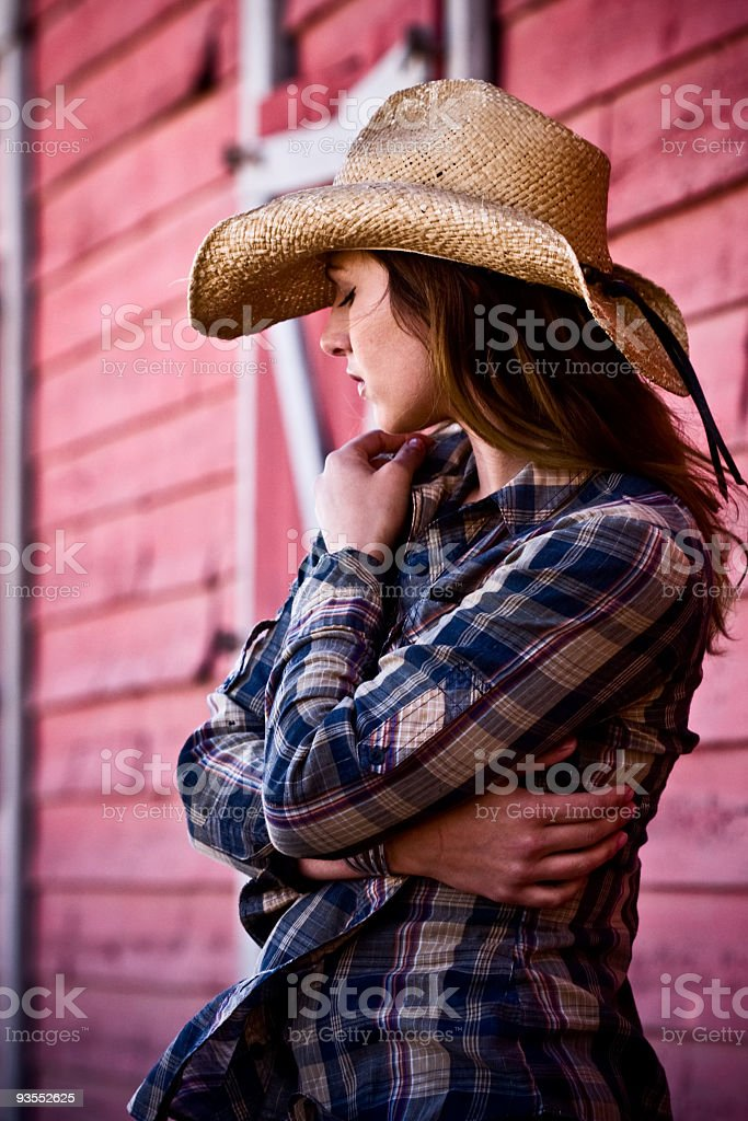 Side view of a cowgirl wearing a plaid flannel and a hat royalty-free stock photo