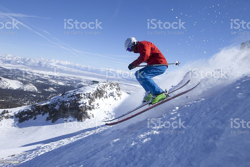 Side view of a fast skier going down a snowy mountain stock photo