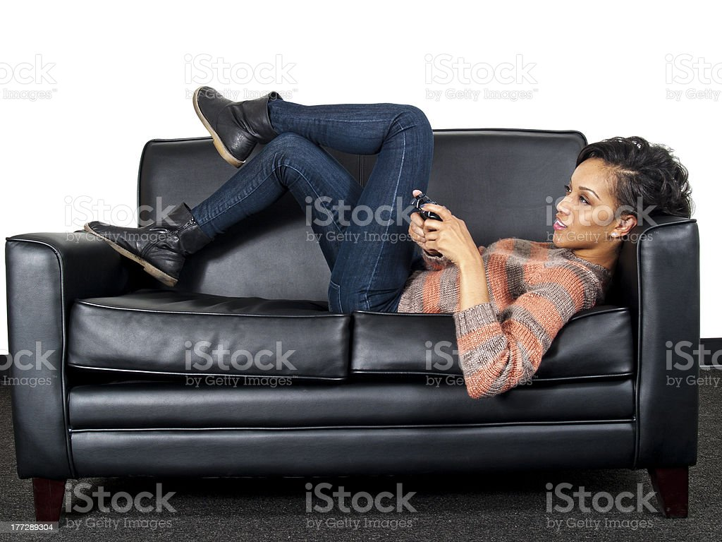Side View of a Female Relaxing and Playing Video Games royalty-free stock photo