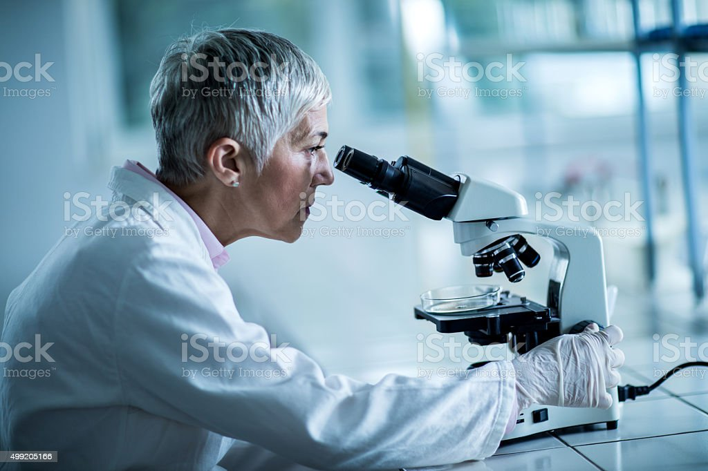 Side view of a female scientist looking through a microscope. stock photo