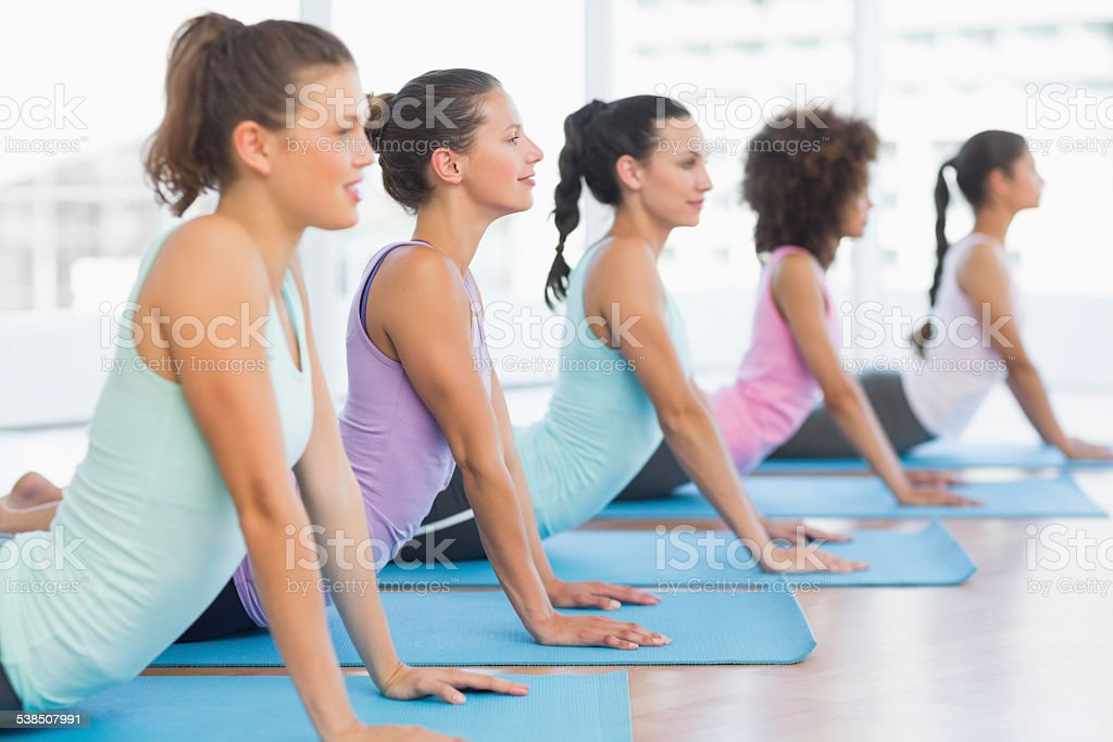 Side view of a fit class doing the cobra pose stock photo
