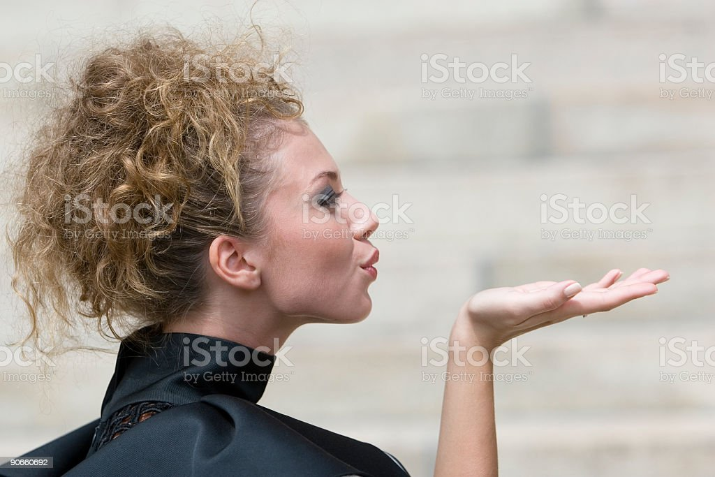 Side view of a pretty female model blowing a kiss stock photo