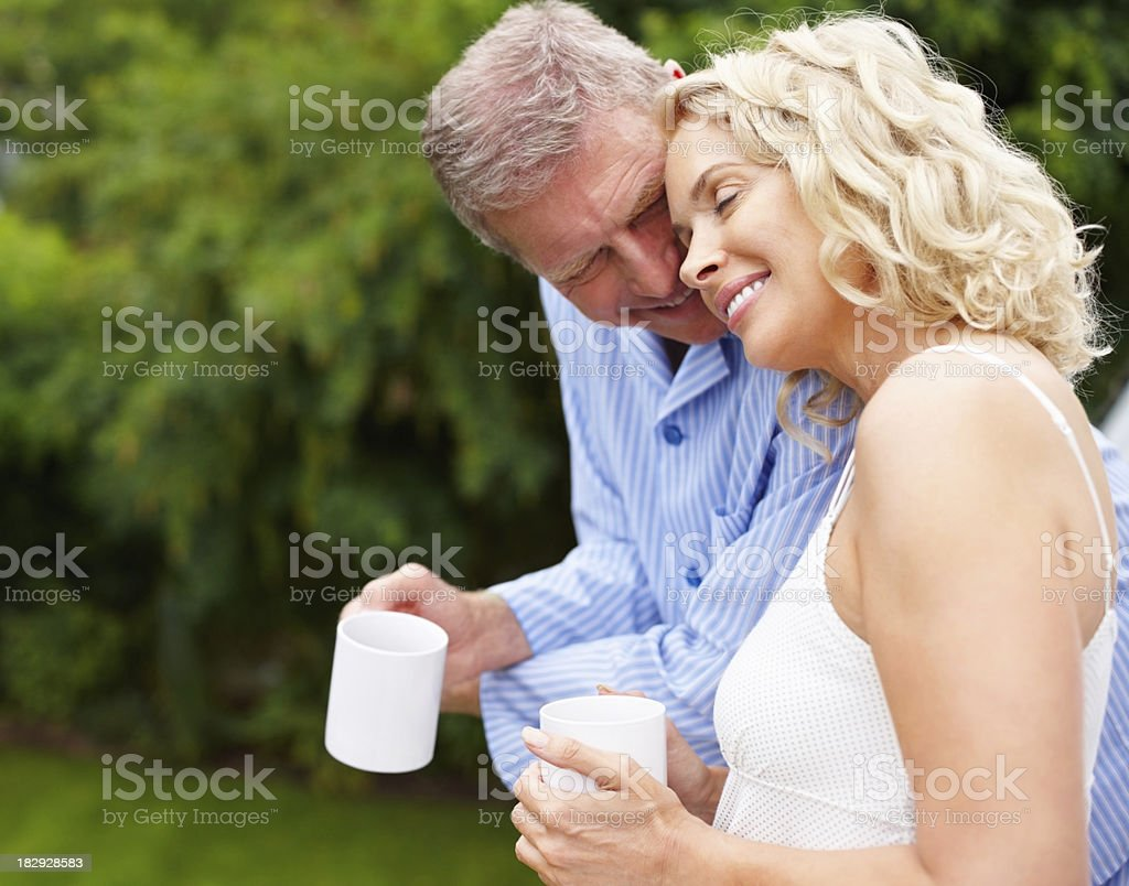 Side view of a romantic mature couple standing outdoors royalty-free stock photo