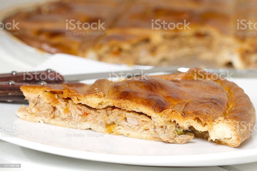 Side view of a slide of Galician pie on white ceramic plate stock photo