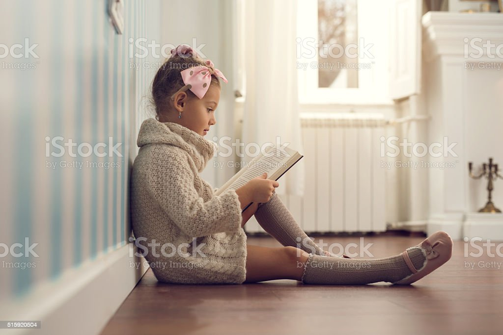 Side view of a small girl reading a book. stock photo