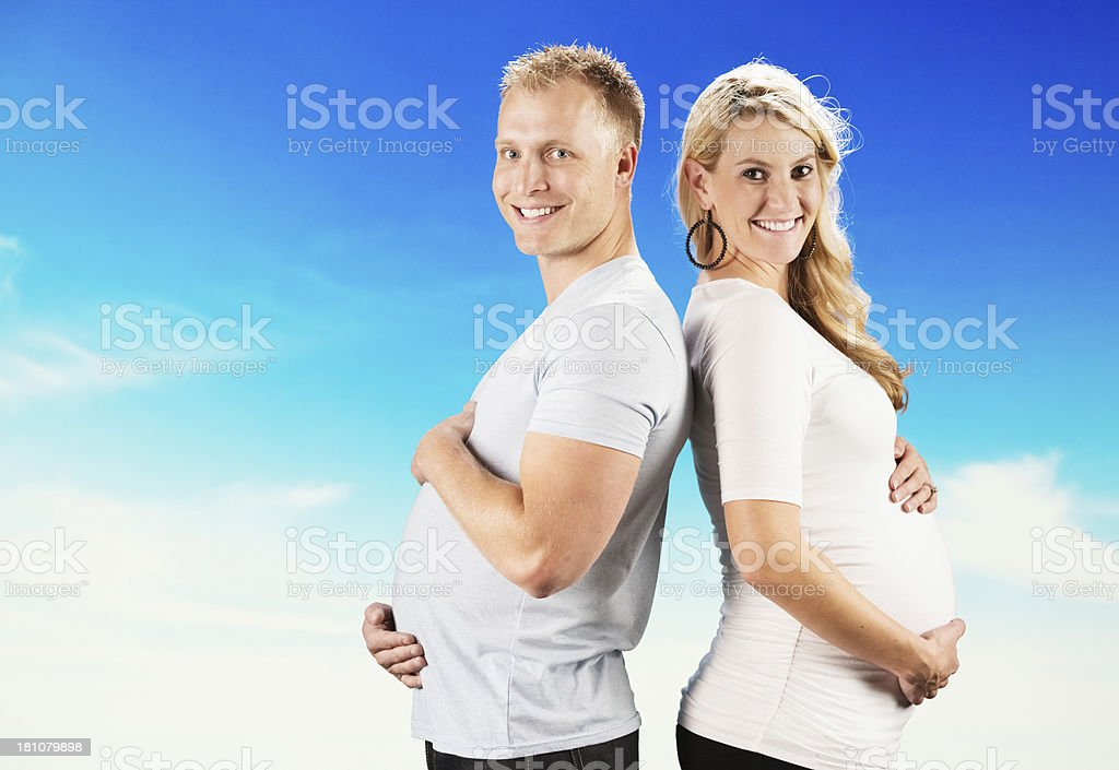 Side view of a smiling couple holding stomach royalty-free stock photo